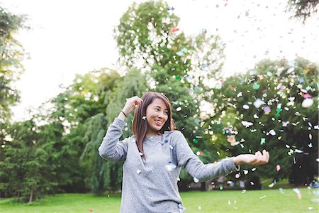 Young woman in park throwing confetti Stock Photo - Premium Royalty-Free, Code: 649-08824082