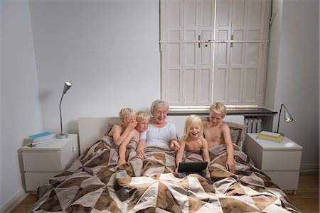 preteen boy shirtless - Grandmother in bed with grandsons using digital tablet Stock Photo - Premium Royalty-Free, Code: 649-08824955
