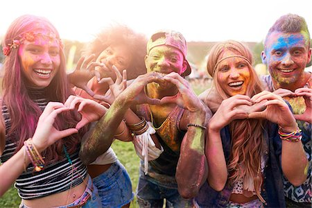 Portrait of group of friends at festival, covered in colourful powder paint, making heart shapes with hands Stock Photo - Premium Royalty-Free, Code: 649-08825189