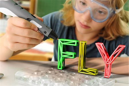 pre-teen boy models - Boy with digital pen and 3D model of capital-lettered word in classroom Stock Photo - Premium Royalty-Free, Code: 649-08840769
