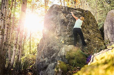 Female boulderer moving up forest boulder, Horne Lake Caves Provincial Park, Vancouver Island, British Columbia, Canada Stock Photo - Premium Royalty-Free, Code: 649-08860006