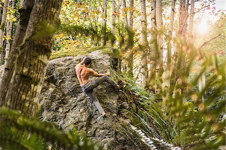 Male boulderer moving up forest boulder, Horne Lake Caves Provincial Park, Vancouver Island, British Columbia, Canada Stock Photo - Premium Royalty-Free, Code: 649-08860007