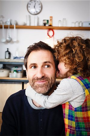 Girl whispering to father in kitchen Stock Photo - Premium Royalty-Free, Code: 649-08894894
