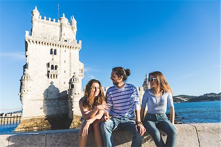 portugal - Three friends, sitting on wall by sea, Belem Tower in background, Lisbon, Portugal Stock Photo - Premium Royalty-Free, Code: 649-08900464