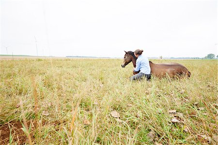 Woman crouching with arm around horse lying down in field Stock Photo - Premium Royalty-Free, Code: 649-08900810