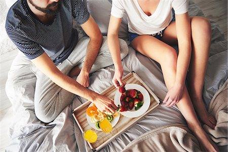 Couple relaxing on bed, eating strawberries, elevated view Stock Photo - Premium Royalty-Free, Code: 649-08902144