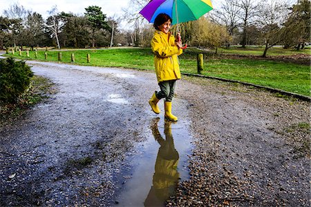 people with umbrellas in the rain - Boy in yellow anorak carrying umbrella in park Stock Photo - Premium Royalty-Free, Code: 649-08902298