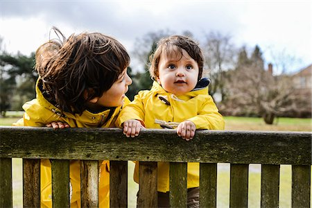 Portrait of baby boy and big brother in yellow anoraks on park bench Stock Photo - Premium Royalty-Free, Code: 649-08902293