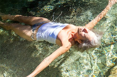 Woman wearing swimsuit arms open floating in water Stock Photo - Premium Royalty-Free, Code: 649-08923333