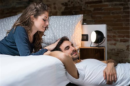 romantic couple bed - Affectionate young couple reclining on bed Stock Photo - Premium Royalty-Free, Code: 649-08949581