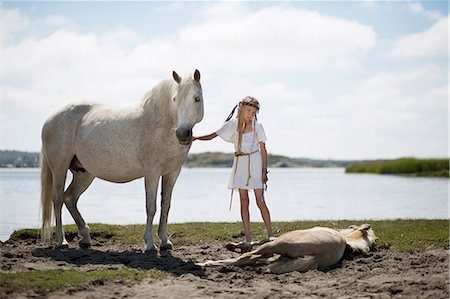 Girl petting horses on sandy beach Stock Photo - Premium Royalty-Free, Code: 649-09003871