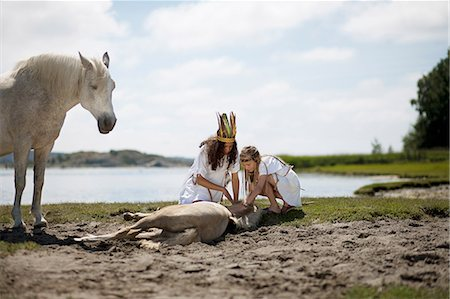 Girls petting horse on sandy beach Stock Photo - Premium Royalty-Free, Code: 649-09003873
