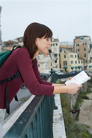 Young woman with travel book reading old city in background. Stock Photo - Premium Royalty-Free, Code: 649-01609902