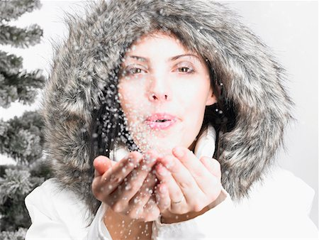 Woman next to a fir-tree, blowing snow Stock Photo - Premium Royalty-Free, Code: 649-02054355