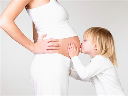 Girl kissing her mother's pregnant belly Stock Photo - Premium Royalty-Free, Code: 649-02198978