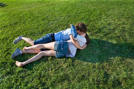 Teen couple laying on grass, kissing Stock Photo - Premium Royalty-Free, Code: 649-02290325
