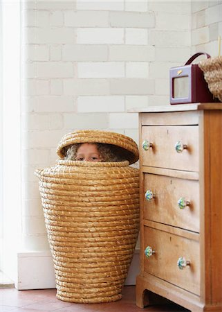Child hiding in laundry basket Stock Photo - Premium Royalty-Free, Code: 649-02424009