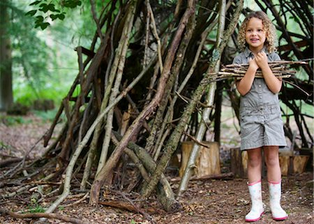 Young girl with pile of twigs in woods Stock Photo - Premium Royalty-Free, Code: 649-02424021