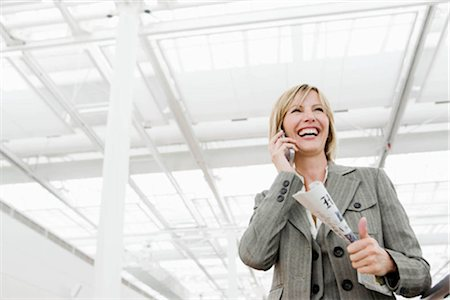 Woman smiling using cell phone Stock Photo - Premium Royalty-Free, Code: 649-02423637
