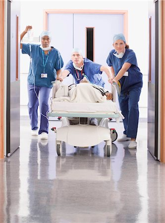 patient walking hospital halls - Three doctors pushing a patient in bed Stock Photo - Premium Royalty-Free, Code: 649-02666333