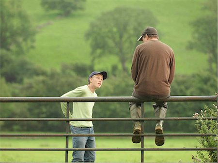 Farmer Talking To Son On Gate Stock Photo - Premium Royalty-Free, Code: 649-02666667