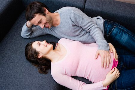 pregnant couple couch - Pregnant woman and man laying on couch Stock Photo - Premium Royalty-Free, Code: 649-02731294