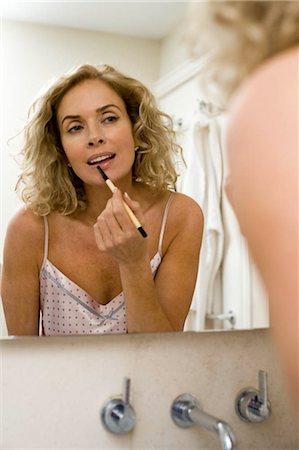 Woman putting on make up Stock Photo - Premium Royalty-Free, Code: 649-02732373