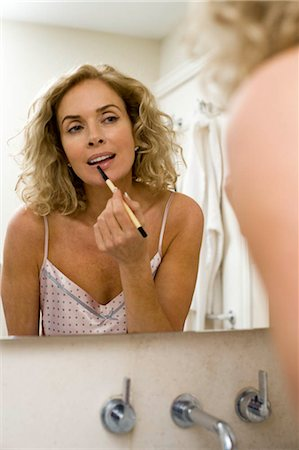 Woman putting on make up Stock Photo - Premium Royalty-Free, Code: 649-02732373
