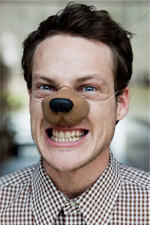 man with toy dog nose snarling Stock Photo - Premium Royalty-Free, Code: 649-03008913