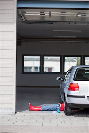 rural gas station - young girl lying under car cleaning Stock Photo - Premium Royalty-Free, Code: 649-03009012