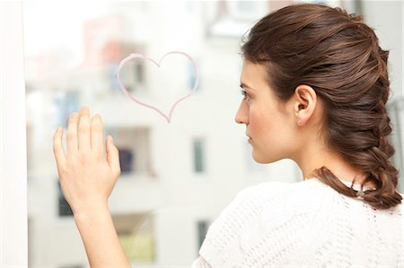Woman looking sadly at a painted heart. Stock Photo - Premium Royalty-Free, Code: 649-03009686
