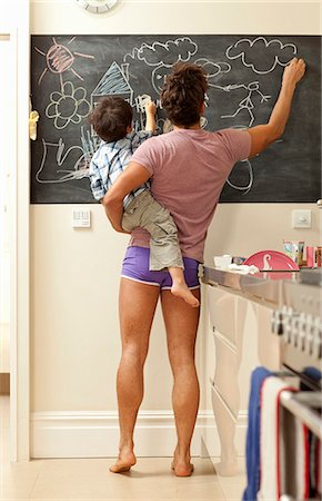 father and son drawing on chalkboard Stock Photo - Premium Royalty-Free, Code: 649-03010123