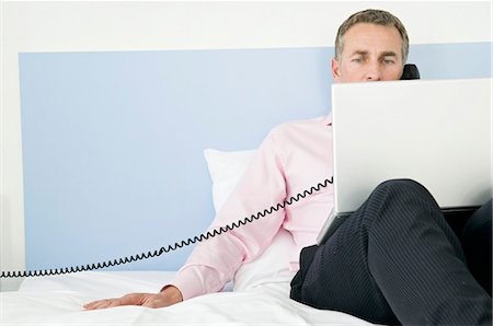 Business man working in his hotel room Stock Photo - Premium Royalty-Free, Code: 649-03010187