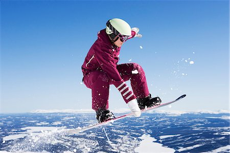 sports and snowboarding - Girl in jumpsuit grabbing board mid-air. Stock Photo - Premium Royalty-Free, Code: 649-03077572