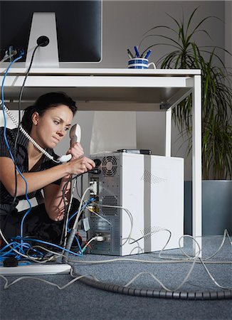 phone cord - A female angrily fixing her computer Stock Photo - Premium Royalty-Free, Code: 649-03077988