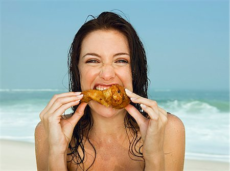 Young women eating a chicken leg Stock Photo - Premium Royalty-Free, Code: 649-03154162