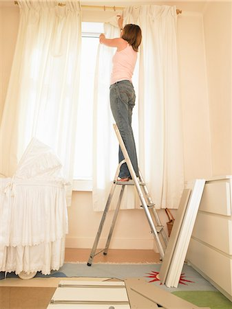 Woman hanging curtains Stock Photo - Premium Royalty-Free, Code: 649-03154231