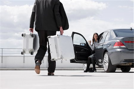 person walking on parking lot - man carrying cases woman waiting in car Stock Photo - Premium Royalty-Free, Code: 649-03154657