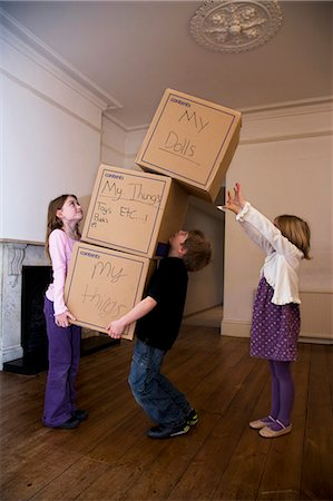 dangerous accident - Three children moving a stack of boxes Stock Photo - Premium Royalty-Free, Code: 649-03153519