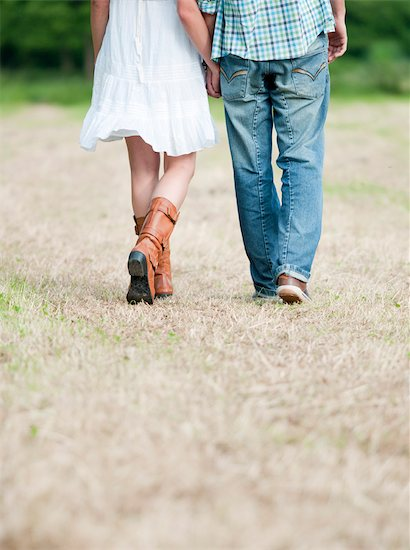 Couple walking in countryside field Stock Photo - Premium Royalty-Free, Image code: 649-03294444