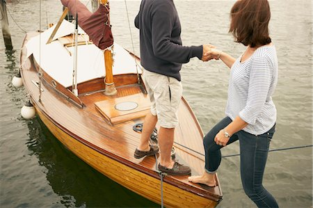 Man helping woman onto old boat Stock Photo - Premium Royalty-Free, Code: 649-03296468