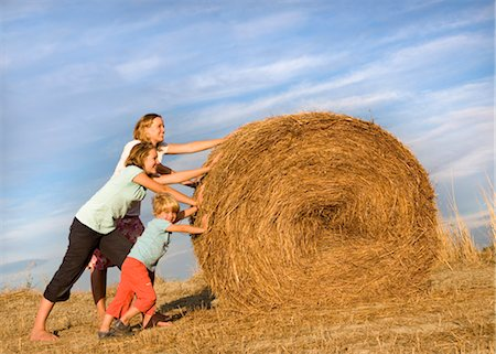 roll (people and animals rolling around) - girl, woman, boy pushing hay bale Stock Photo - Premium Royalty-Free, Code: 649-03296605