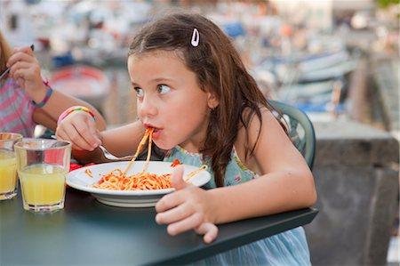 girl eating spaghetti Stock Photo - Premium Royalty-Free, Code: 649-03296733