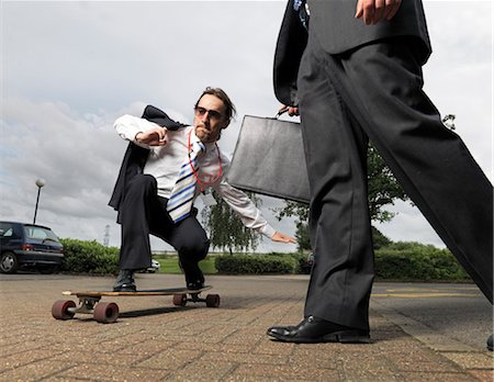 person walking on parking lot - businessman on skateboard Stock Photo - Premium Royalty-Free, Code: 649-03292127