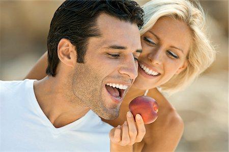 A female feeding a latin man an apple. Stock Photo - Premium Royalty-Free, Code: 649-03292925