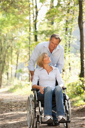 Man pushes woman in a wheelchair Stock Photo - Premium Royalty-Free, Code: 649-03363300