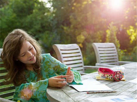 preteens fingering - Young girl counting on fingers in garden Stock Photo - Premium Royalty-Free, Code: 649-03363353