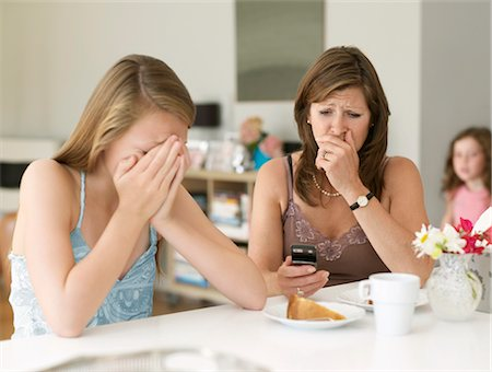 mother sees cyber bullying on cellphone Stock Photo - Premium Royalty-Free, Code: 649-03363370