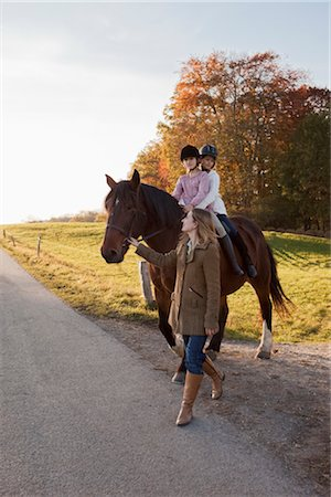 equestrian - Woman walking a horse with two girls Stock Photo - Premium Royalty-Free, Code: 649-03418544