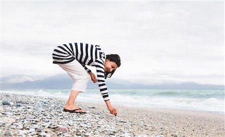 Woman picking shells on a beach Stock Photo - Premium Royalty-Free, Code: 649-03446850